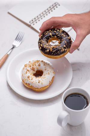 Working desk with dessert and coffee. Cake donuts with a cup of espresso on marble table top.
