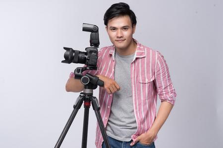 Jonge Aziatische fotograaf die digitale camera houdt, terwijl het werken in studio