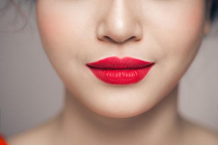 Mooie perfecte lippen. De jonge Aziatische vrouw van de schoonheid Lippen over witte achtergrond