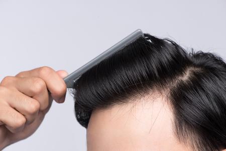 Close up Foto von sauberen gesunden Mannes Haar. Junger Mann kämmt seine Haare