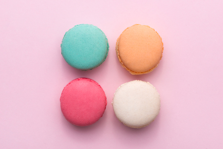 Colorful pastel cake macaron or macaroon on pink background from above