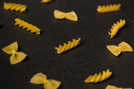 Pattern made of pasta on dark background. Stock Photo