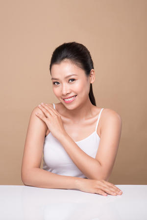 Schoon huidconcept. Jonge Aziatische vrouw aan haar schouder te raken