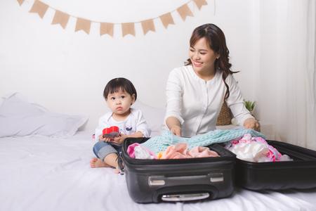 Aziatische moeder en babymeisje met kofferbak en kleding klaar om op vakantie te reizen Stockfoto