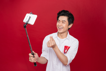 narcissist: Happy young asian man taking self portrait photography through smart phone over red background.