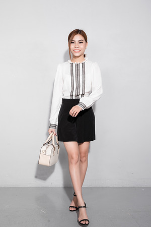 Beautiful happy asian woman holding a bag walking over gray background.