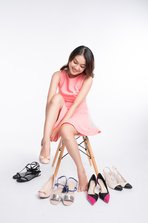 Pretty young asian woman trying on a few pairs of high heels Stock Photo