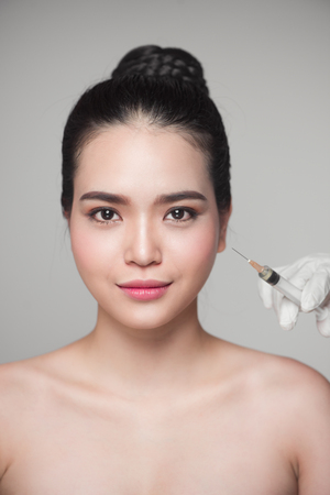 dermal: Beautiful asian woman gets beauty facial injections. Face aging injection. Stock Photo