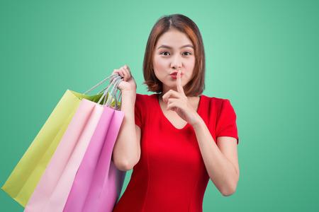 Mooie jonge Aziatische vrouw met gekleurde boodschappentassen over blauwe achtergrond