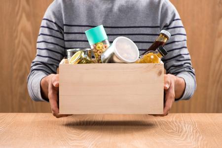 Bénévole avec une boîte à dons avec des denrées alimentaires sur fond de bois Banque d'images - 79284732