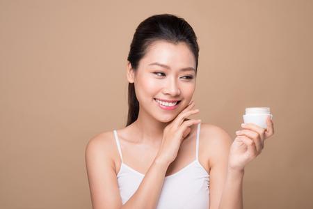 Cura della pelle. Bella donna asiatica mostra crema idratante o lozione prodotto. Archivio Fotografico - 79304873