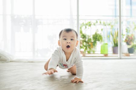 小さなかわいい女の子の家の床の上でクロール