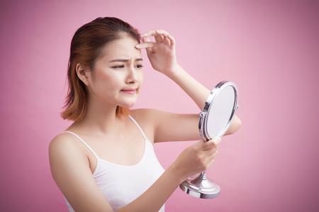 Vrij jonge Aziatische vrouw die een spiegel houdt, raakt en zich ongerust maakt over haar gezicht