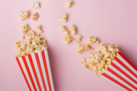 Popcorn in red and white cardboard box on the pink background. Reklamní fotografie