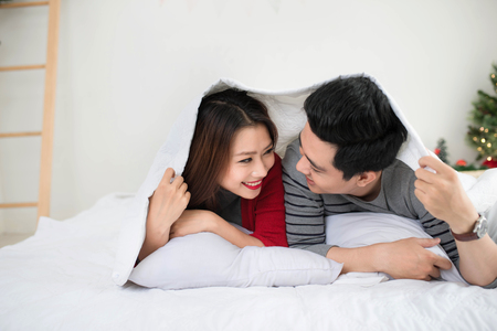 Couple in love sharing genuine emotions and happiness lying on bed. Banco de Imagens