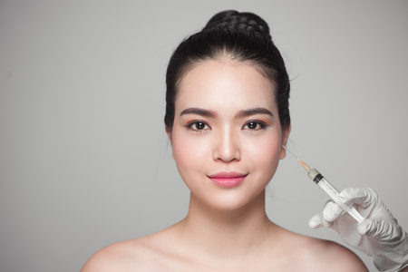 Beautiful asian woman gets beauty facial injections. Face aging injection. Stock Photo
