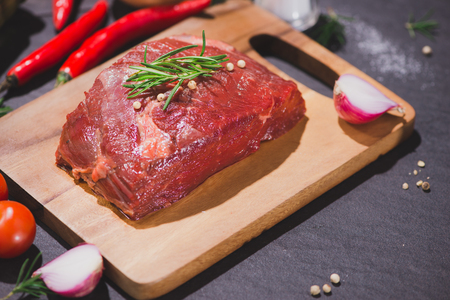 Raw beef on a cutting board  with spices and ingredients for cooking.