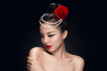 Fashion studio shot of beautiful young asian woman with retro hairstyle. Portrait with Red Rose flower