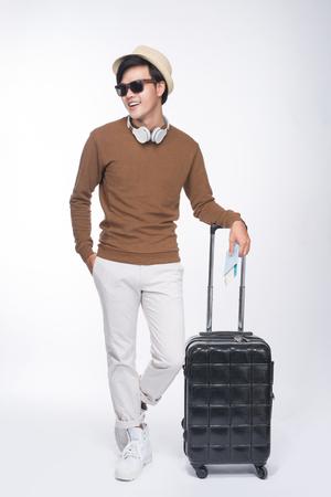 회색 배경 위에 가방 여권을 들고 젊은 관광 아시아 사람의 전체 길이