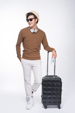 Full length of young tourist asian man holding passport with suitcase over grey background Stockfoto