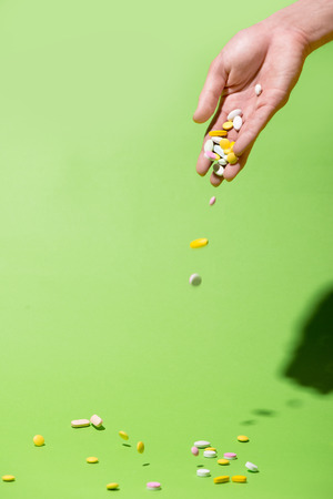 Colored pills falling from hand on green background.