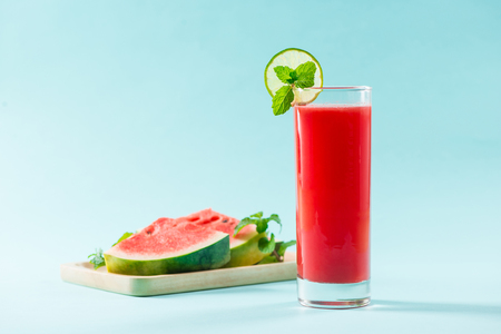 Glass of healthy watermelon juice in summertime on blue background.