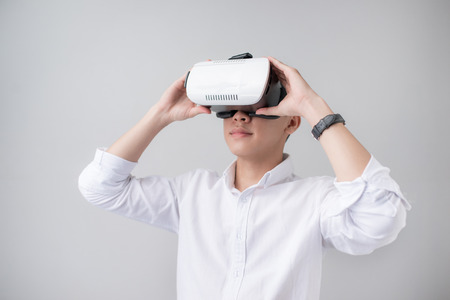visualizing: Excited asian man in a VR goggles and gesturing with his hands