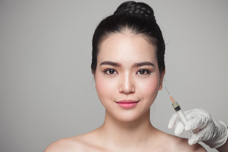 Beautiful asian woman gets beauty facial injections. Face aging injection. Imagens