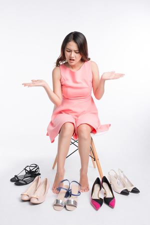 Pretty young asian woman having difficult choice to try on a few pairs of high heels Stock Photo