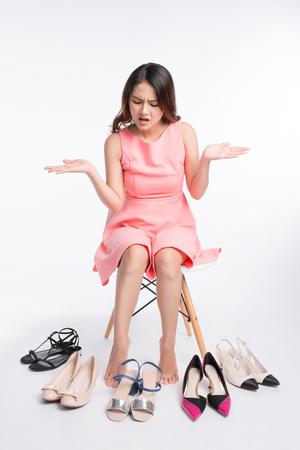 Vrij jonge Aziatische vrouw die moeilijke keus heeft om op een paar paren hoge hielen te proberen Stockfoto