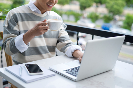 businessman working at his computer: Handsome asian young man working on laptop and smiling while enjoying coffee in cafe Stock Photo