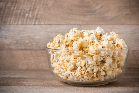 buttered: Popcorn in a bowl on the wooden table.
