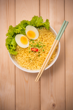 Instant noodles in bowl with vegetables and  boiled egg on wood background