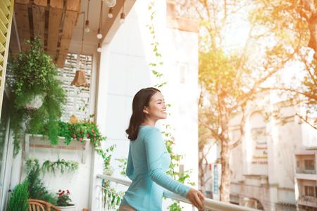 Hermosa chica asiática disfrutando de la frescura en el balcón Foto de archivo - 80104975