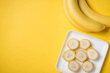 バナナと黄色の背景の上皿にスライスしたバナナの花束。