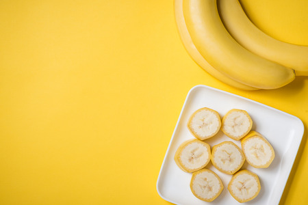 A banch of bananas and a sliced banana in a dish over yellow background. Stock Photo