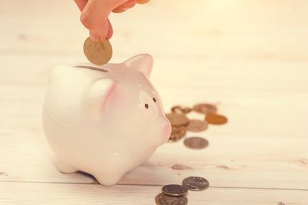 핑크 돼지 저금통에 황금 동전을 퍼 팅하는 손. 일본 엔. 스톡 콘텐츠
