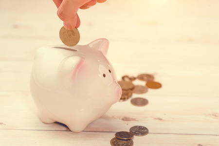 Hand putting golden coins into a pink piggy bank. Japanese Yen. Фото со стока
