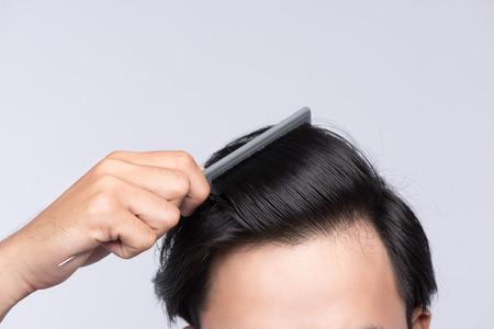 깨끗한 건강한 남자의 머리카락 사진을 닫습니다. 젊은 남자가 그의 머리를 빗어