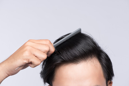 Close up photo of clean healthy man's hair. Young man comb his hair Standard-Bild