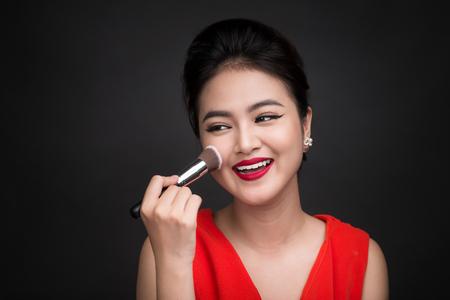 Kosmetische Puderpinsel . Asiatische Frau , die Blusher auf ihre Wangen mit perfektem Make-up und roten Lippen anwendet Standard-Bild - 80105264
