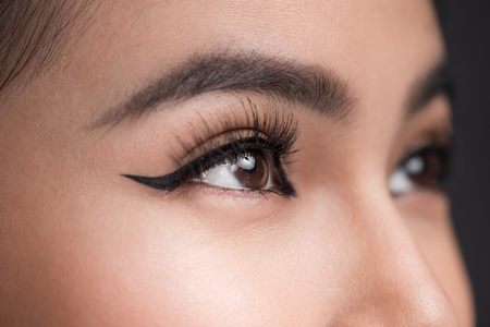Perfect shape of eyebrows. Beautiful macro shot of female eye with classic eyeliner makeup. Stock Photo