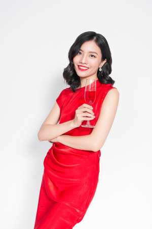 Young celebrating asian woman in red dress holding wine glass. Stock Photo