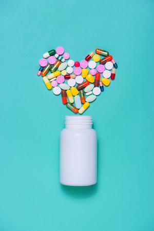 Gekleurde pillen in hartvorm met fles op blauwe achtergrond. Stockfoto