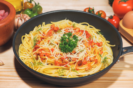 Tasty spaghetti with tomato sauce and meat in pan on wooden table.