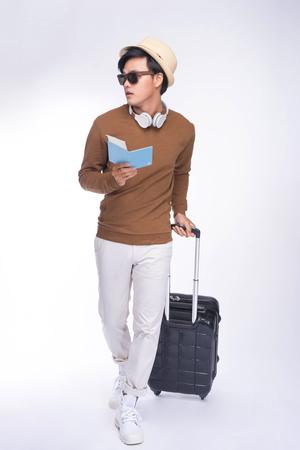 Longitud total de joven asiático hombre celebración pasaporte con maleta sobre fondo gris Foto de archivo - 80105683