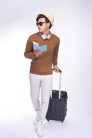 Full length of young asian man holding passport with suitcase over grey background Stockfoto