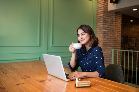 Beautiful cute asian young businesswoman in the cafe, using laptop and drinking coffee smiling Imagens