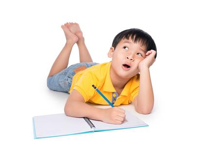 Schooljongen die op een vloer liggen, omhooggaand en in notitieboekje schrijven kijken. Stockfoto