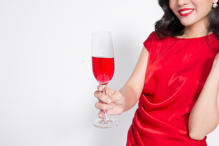 Young celebrating beautiful asian woman in red dress holding wine glass.